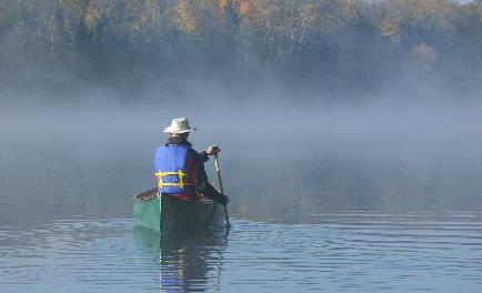 photo of a man paddling a canoe on a misty lake